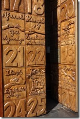 Wooden doors with carved panels representing commitments in the new constitution